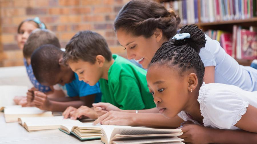 A Teacher assisting her students while reading.