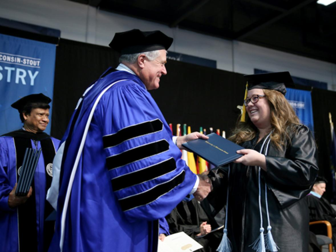 Chancellor Bob Meyer congratulates graduate Grace Sutula as she crosses the stage at commencement Saturday, Dec. 16, in Johnson Fieldhouse. Sutula earned a degree in applied mathematics and computer science.