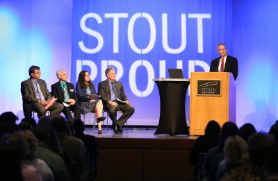 Pictured on stage at the podium is Phil Lyons, Vice Chancellor for Administrative and Student Life Services. Seated from left is Charles Bomar, Dean of the STEM College; Patrick Guilfoile, Provost and Vice Chancellor for Academic and Student Affairs; Meridith Drzakowski, Assistant Chancellor; and Bob Meyer, Chancellor.
