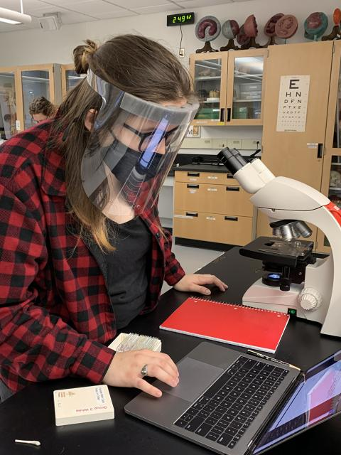 Erin Hongerholt, wearing one of 3,000 face shields donated to UW-Stout by Prent Corp., works at a microscope during her Human Biology course lab in Jarvis Hall Science Wing.
